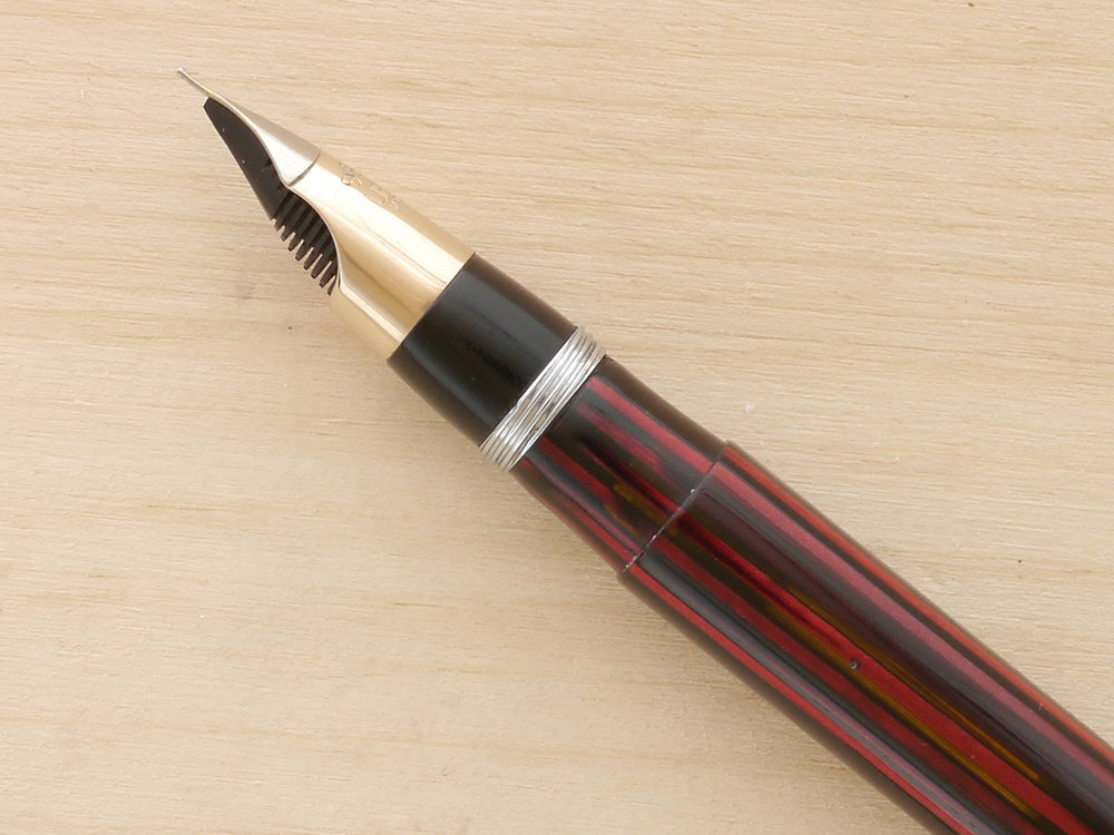 Sheaffer White Dot Lifetime Triumph Vac filler, nib profile showing excellent geometry and alignment. Also, note the orange tones in the barrel showing transparency (the background showing through).
