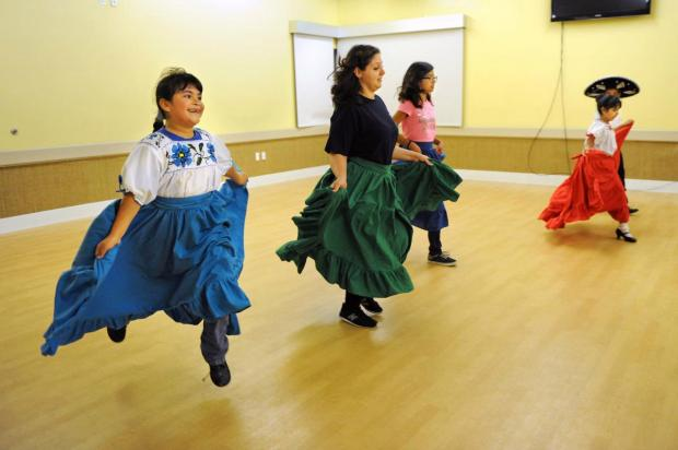 Ariana Berumen, 7, left, enjoys a ballet folklorico class with instructor Charity Jackson and Saray Perez, 11; Lisette Perez, 7; and brother Eric Perez, 10; at Riverside's Bryant Park Community Center on Nov. 6. The Riverside Arts Academy offers free and low-cost dance, music and art classes at three local community centers.