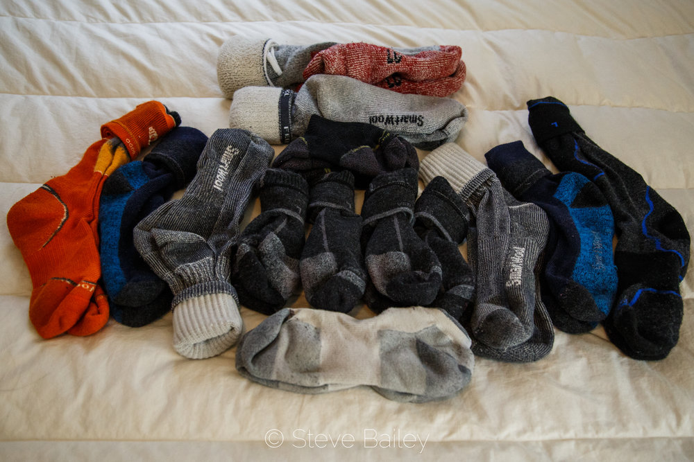 The current collection: SmartWool PhD Backcountry socks (orange), 2 pair discontinued Smartwool socks (blue), 3 pair Smartwool Hike Medium Crew (grey), Smartwool Mountaineering Extra Heavy Crew Socks (red), Smartwool PhD Outdoor Medium Crew Socks (black and green), 4 pair Darn Tough 1/4 Cushion socks (black and grey), Darn Tough No Show Light socks (cream and grey), and Darn Tough Over-the-Calf Padded Light (black and blue).