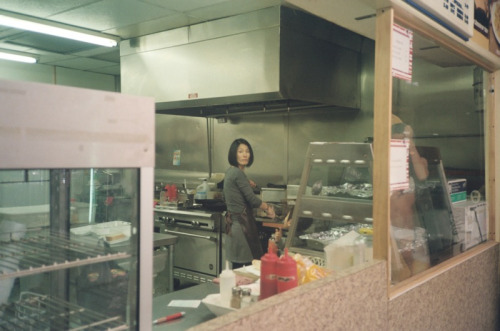 my cousin in the kitchen of her convenience store frying chicken