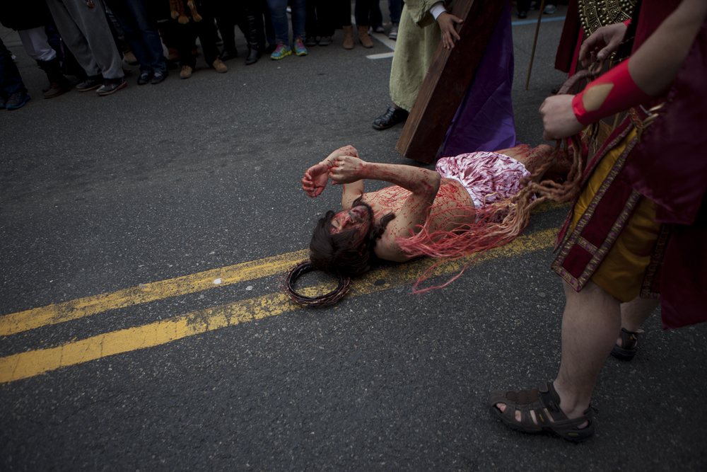 Elmer Ventura, as Jesus, falls to the ground as onlookers watch. Many wept.