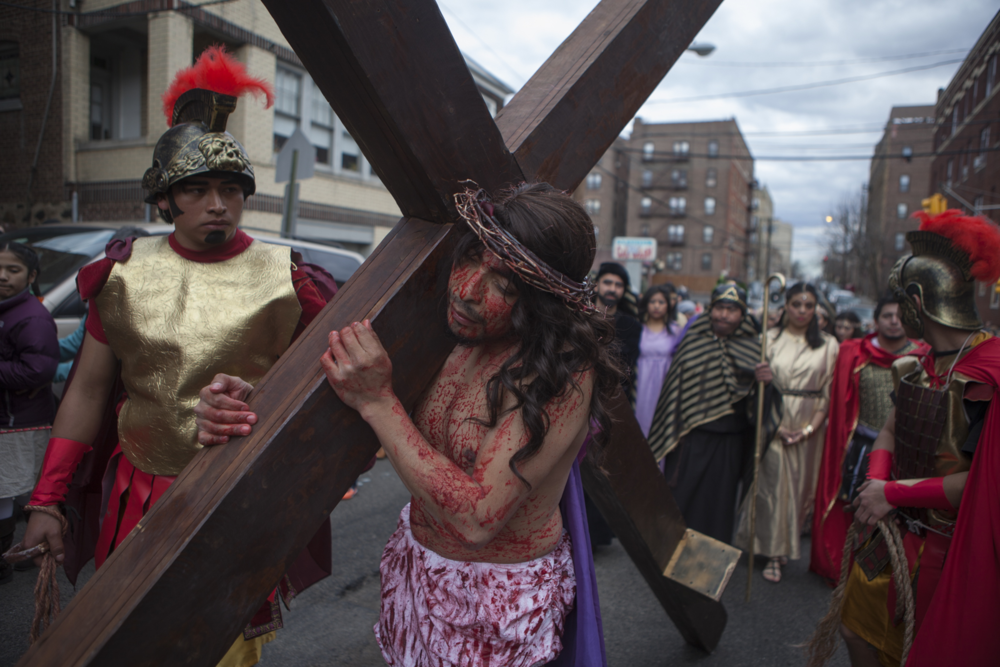 Elmer Ventura, as Jesus, carries a cross during the Stations of the Cross procession. Members of St. Joseph of the Palisades performed in Spanish and marched from one church to another down the city.