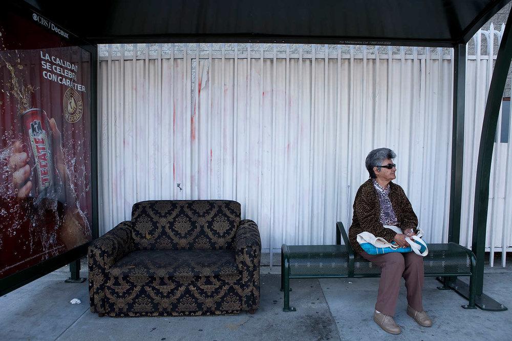 EAST LOS ANGELES, LE 11 MAI 2011: Une femme Latina partage un abris bus avec un vieux canapé et une publicité en espagnol pour Tecate, une bière Mexicaine, sur Cesar Chavez Avenue (l'organisateur des travailleurs Mexicains) à East LA, le quartier Latino historique de Los Angeles (plus de 98% d'habitants Latinos), où commence l'intinéraire. Les Latinos représentent la grande majorité des utilisateurs des transports public à Los Angeles (photo Gilles Mingasson pour Le Monde2).