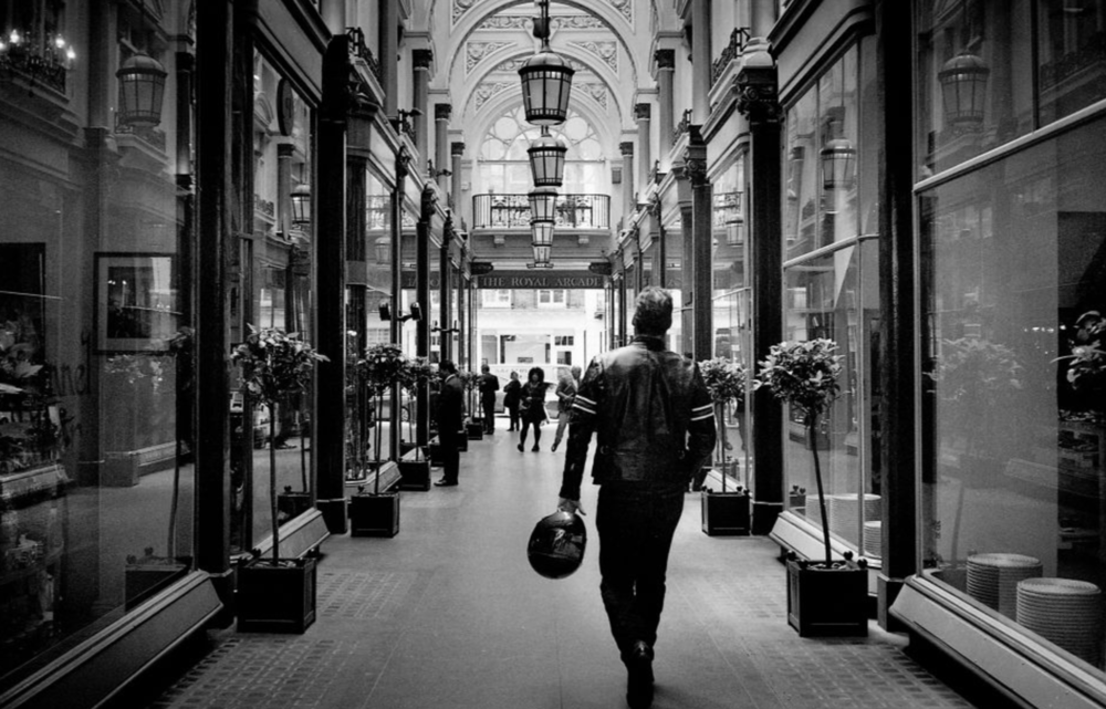 Biker on the Royal Arcade, Bond Street, London, England (18th June 2012)  // Minolta Hi-Matic AF2, Ilford XP2 400, Epson V330. I've always been interested in combining opposites - old with new, east with west, heritage with innovation. I enjoyed the perspective in this moment: both the perspective of looking down the Royal Arcade and the perspective of how well the Royal Arcade, a Victorian shopping arcade built in 1879, related to the motorcyclists outfit.