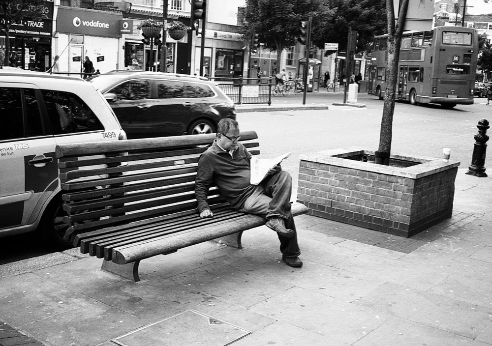 Reading 'out of home', Notting Hill Gate, London, England (Summer 2012)  // Kodak T- Max 100, Zorki - 4, Epsom V330 // Sometimes you just need space that your home cannot provide for you. Sometimes you want noise. Sometimes you want to watch the people walk by or eaves drop on a conversation at the end of a newspaper. And sometimes the confines of your personal living space cannot fulfil all your needs. What better location than outside tube station?