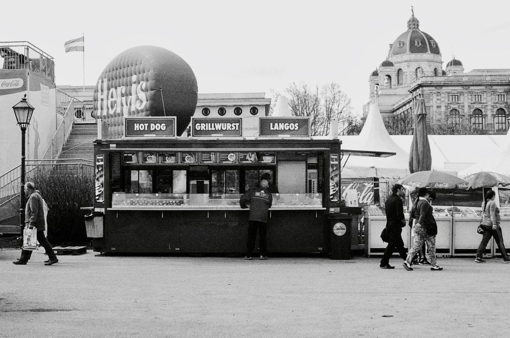 Tourist Attraction, Vienna, Austria (Spring 2013)  // Kodak T-max 100, Olympus OM2n, Epson V330 // The food truck, an icon since 1886. Charles Goodnight, a Texas cattle rancher, fitted a sturdy old United States Army wagon with interior shelving and drawers, and stocked it with kitchenware, food and medical supplies. Food consisted of dried beans, coffee, cornmeal, greasy cloth-wrapped bacon, salt pork, beef, usually dried or salted or smoked, and other easy to preserve food stuffs. The wagon was also stocked with a water barrel and a sling to kindle wood to heat and cook food.