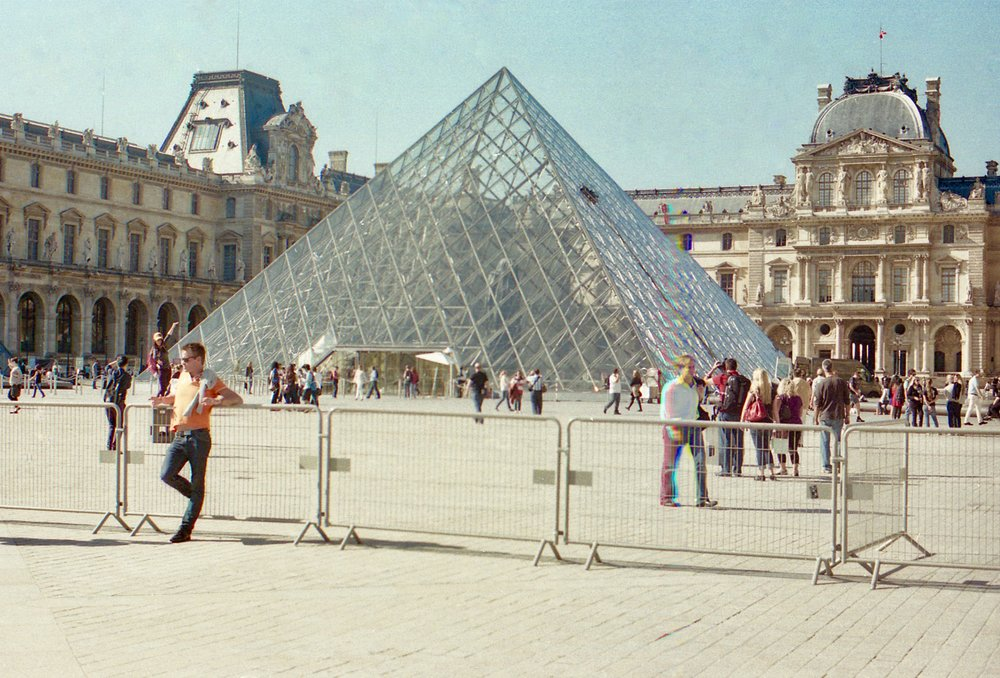 Musee du Louvre, Paris, France, 2013 // Olympus Om-2n, Kodak Portra 160, Epson V330 //  As you can see at the far left at the back, a foreign couple do the ritual of making it look they are touching the top of the building. It makes me reflect on how much does a ritual make a place? How many of our rituals  connect us to a tribe? What else is behind people taking the same photo at a monument? Another accident which I quite like is the rainbow effect on one of the passers by. If only I could work out how to replicate that.