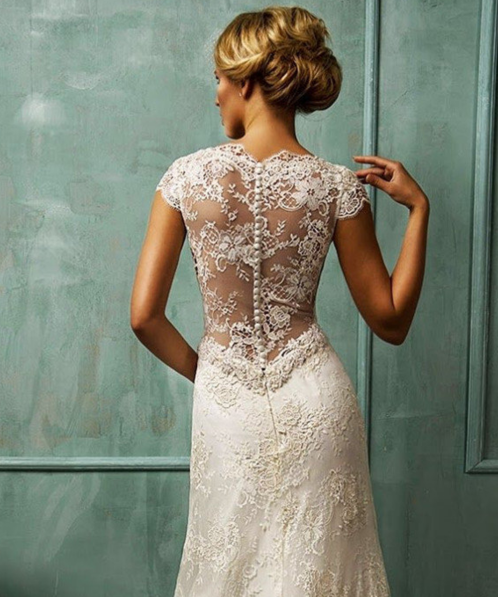 Vintage Inspired Weddings - Ivory lace is often included in vintage inspired wedding dress trend. With the buttons all the way down the back of the dress, this gown exudes vintage elegance.