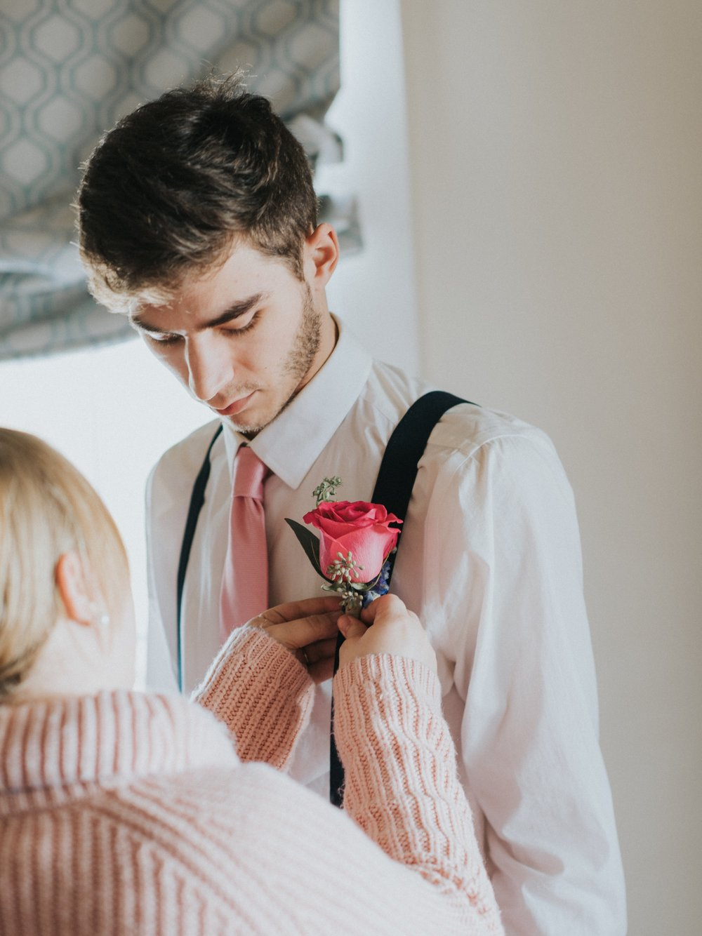 Pinning a boutonniere Louisiana wedding
