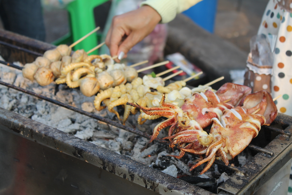 Street vendors hawking seafood balls and grilled squid