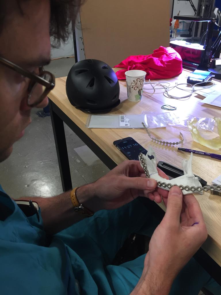 DJ practicing bending a mandibular reconstruction plate on a 3D printed model