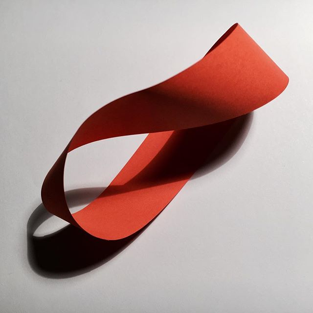 A Möbius strip seemingly intertwined with its own shadow.