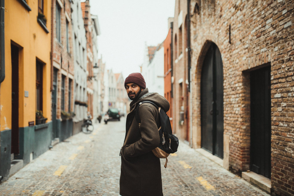 man in beanie looking at camera in bruge town