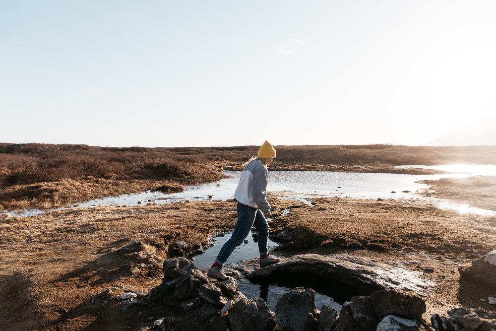 Girl in beanie walking over natural hot spring during sunset in Iceland