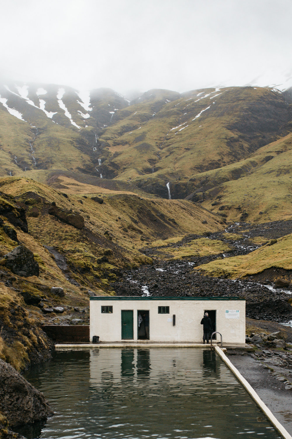 Seljavellir pools in Iceland with mountains in the background