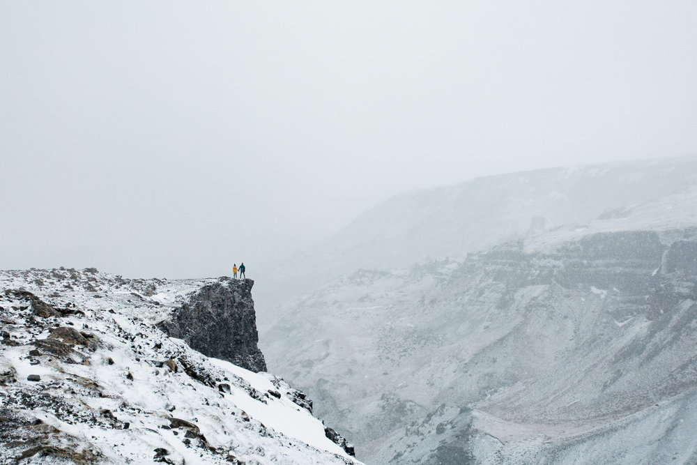 Two people on a cliff in iceland whilst it is snowing