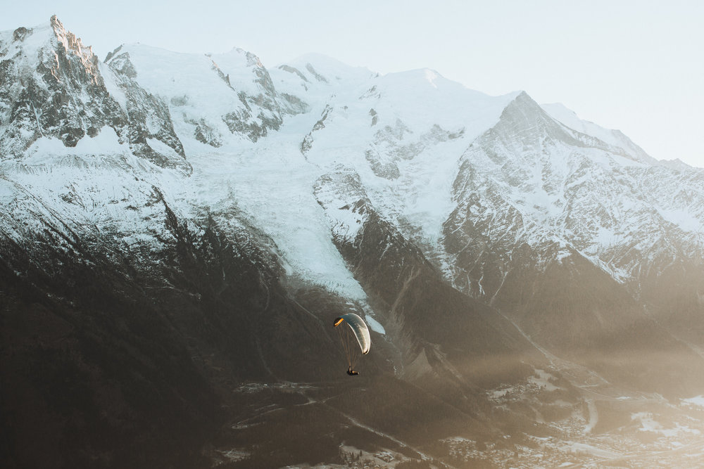 man paragliding during sunset in french alps with mountains in background