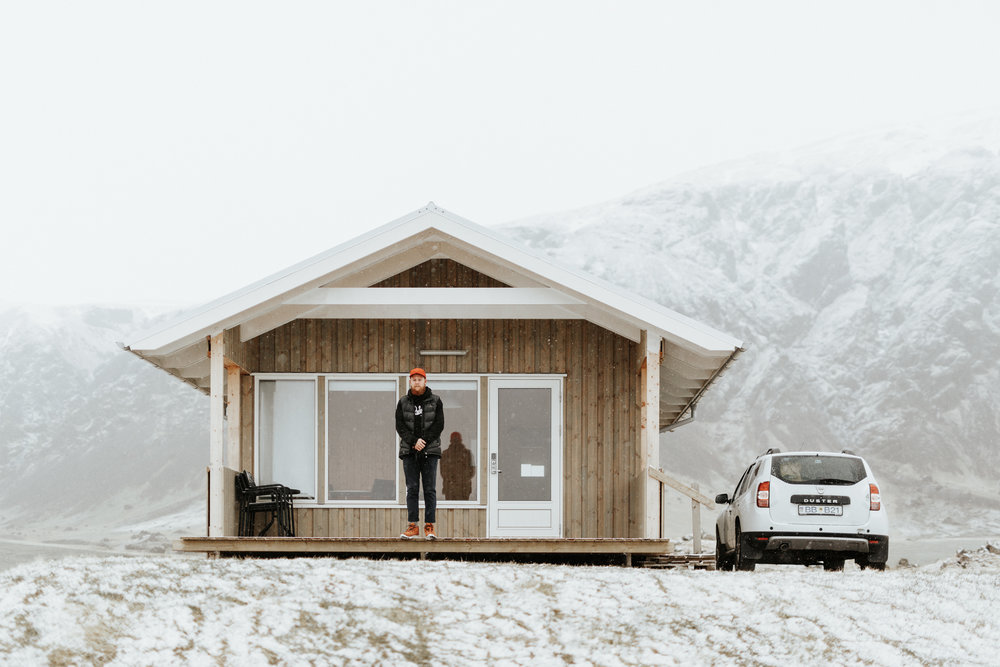 man in front of cabin in iceland with mountains in background with snow everywhere