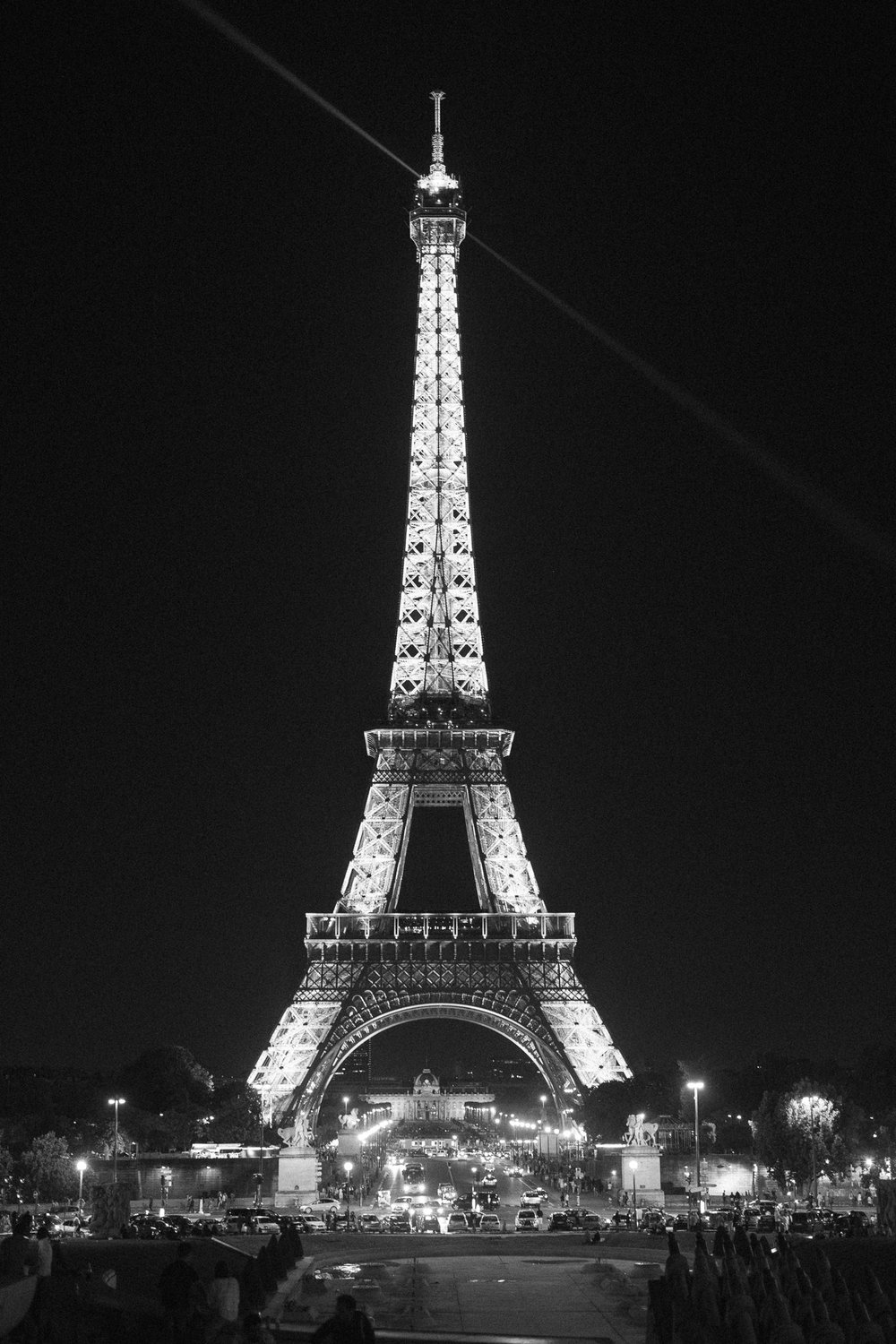 Black and white photo of eiffel tower lit up at night