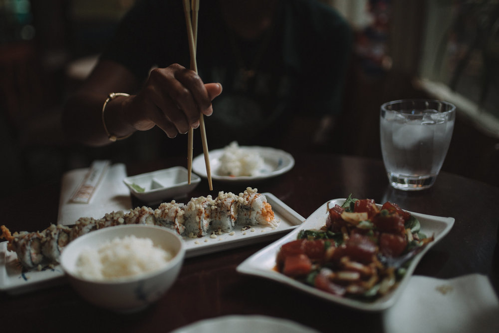chop sticks picking up sushi in dimmly lit cafe in honolulu