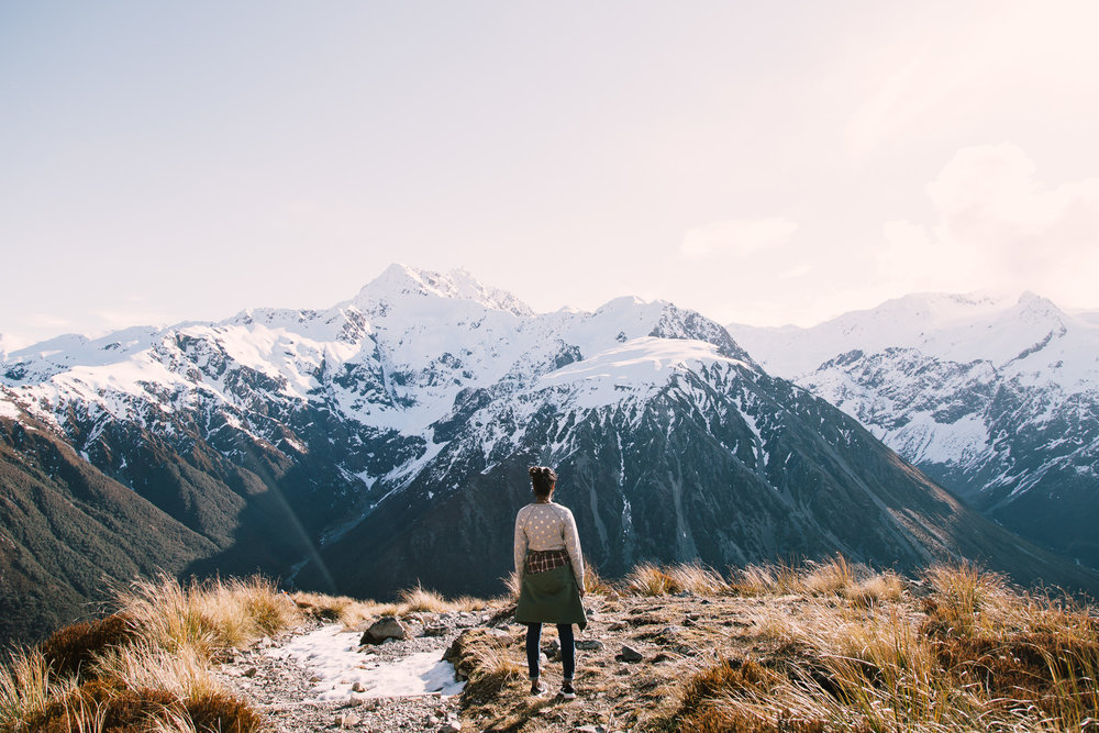 girl overlooking snow capped mountains in background while on top of mountain