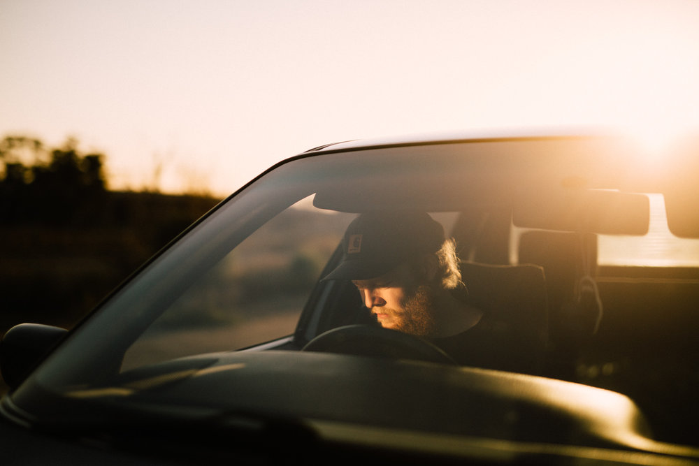 driver in car with sun on face during sunset