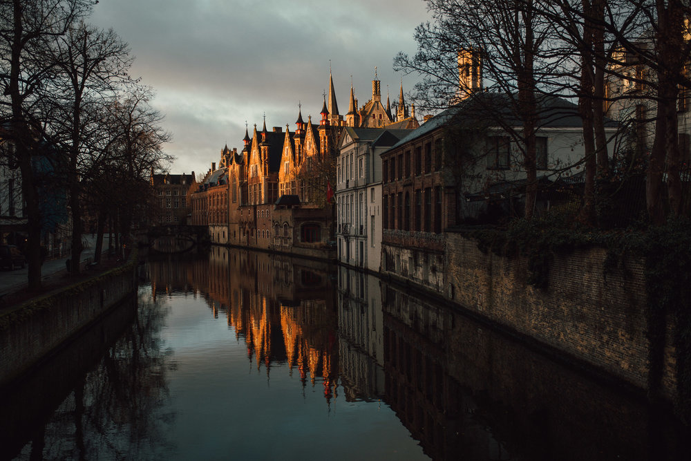Buildings in Bruge lit during sunrise in town with canal in foreground