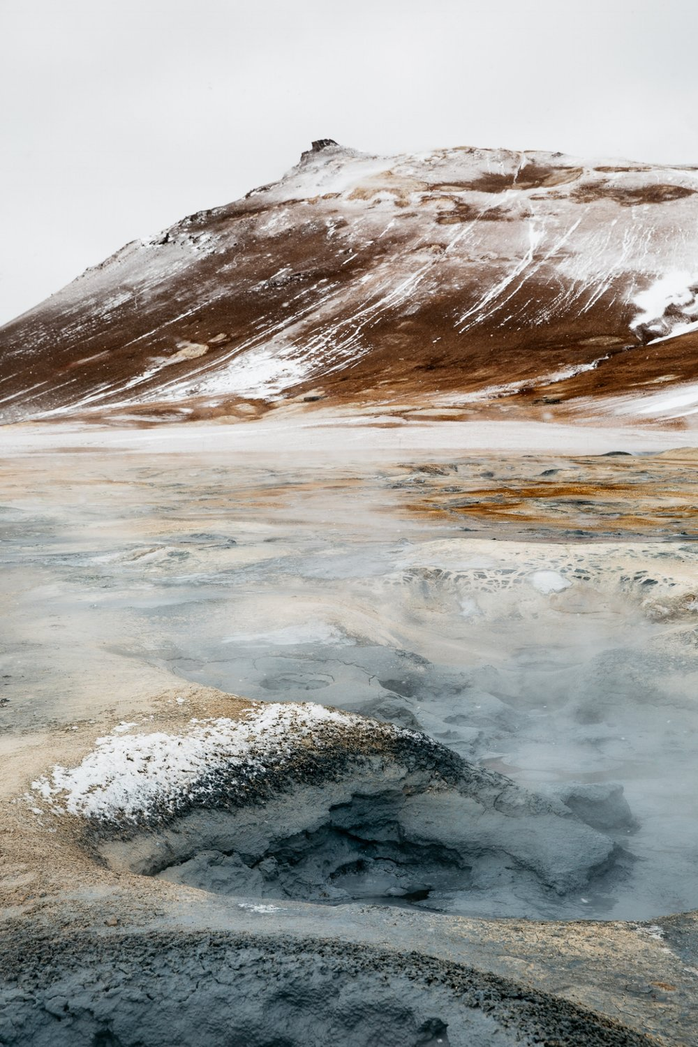 geothermal activity in iceland with snow capped mountain in background
