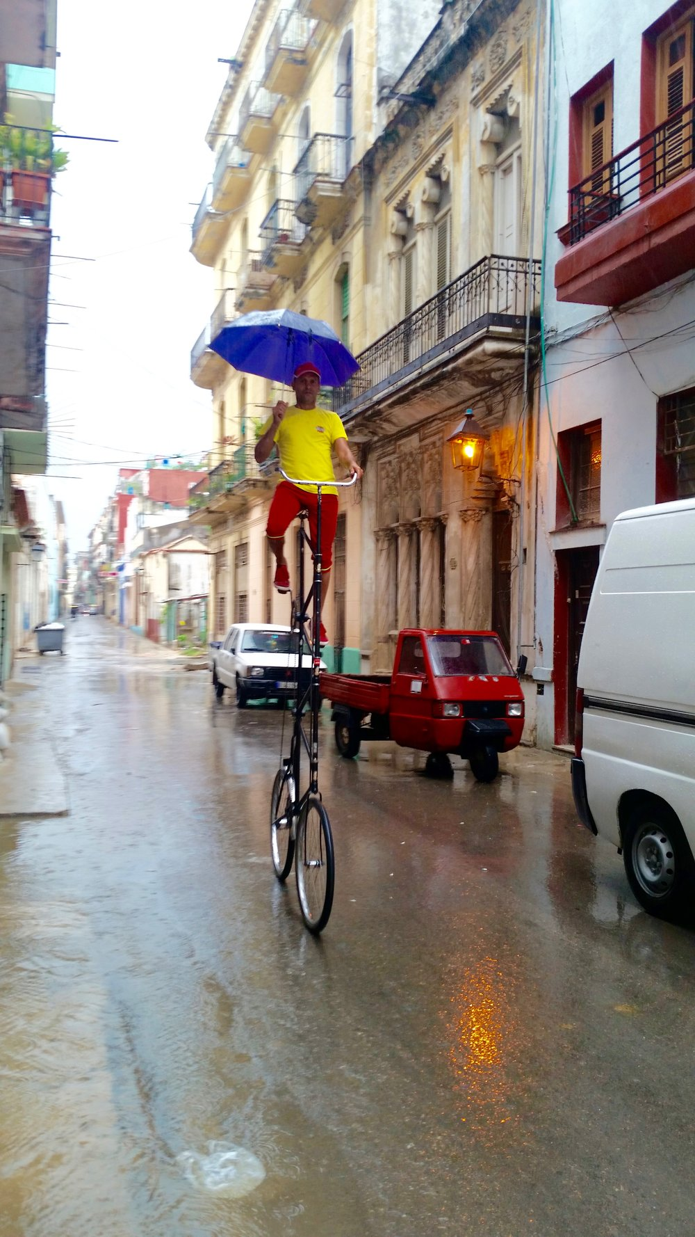 Felix Guirola riding his bike on a rainy day in Old Havana