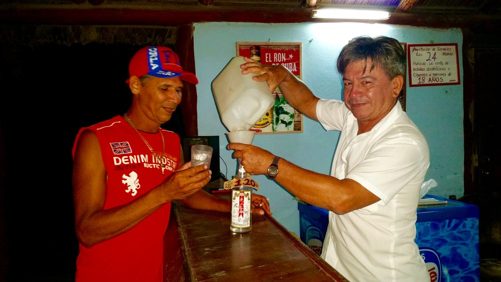A bartender in Santa Lucia, Camaguey, pours beer from a jug from a recycled jug into a recycled bottle