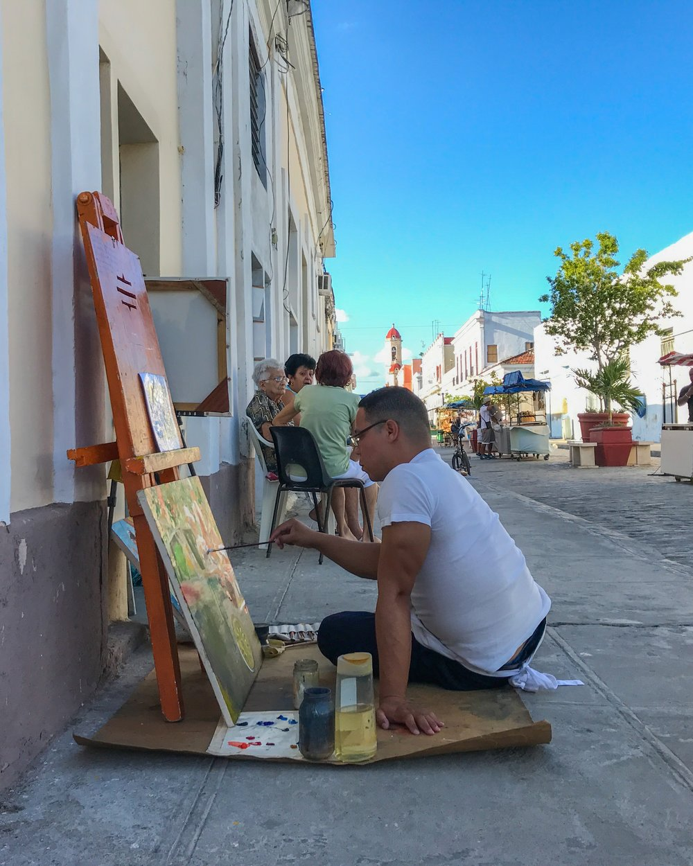 An artist painting on the street in Cienfuegos before giving us a tour of his gallery