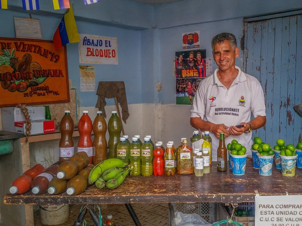 A vendor in Sancti Spiritu sells homemade sauces, pickles, and purees out of old rum and water bottles