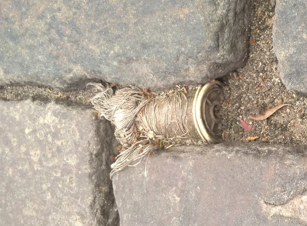 Thread is everywhere ! (spool found in Berlin's cobblestone pavement...)