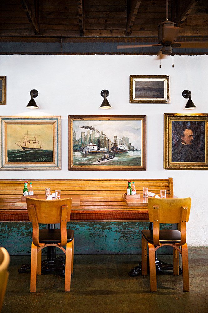 A straight row of art accentuated by overhead lighting, at Leon's Fine Poultry and Oysters in Charleston, South Carolina. Photo by Brittany Ambridge for Domino.