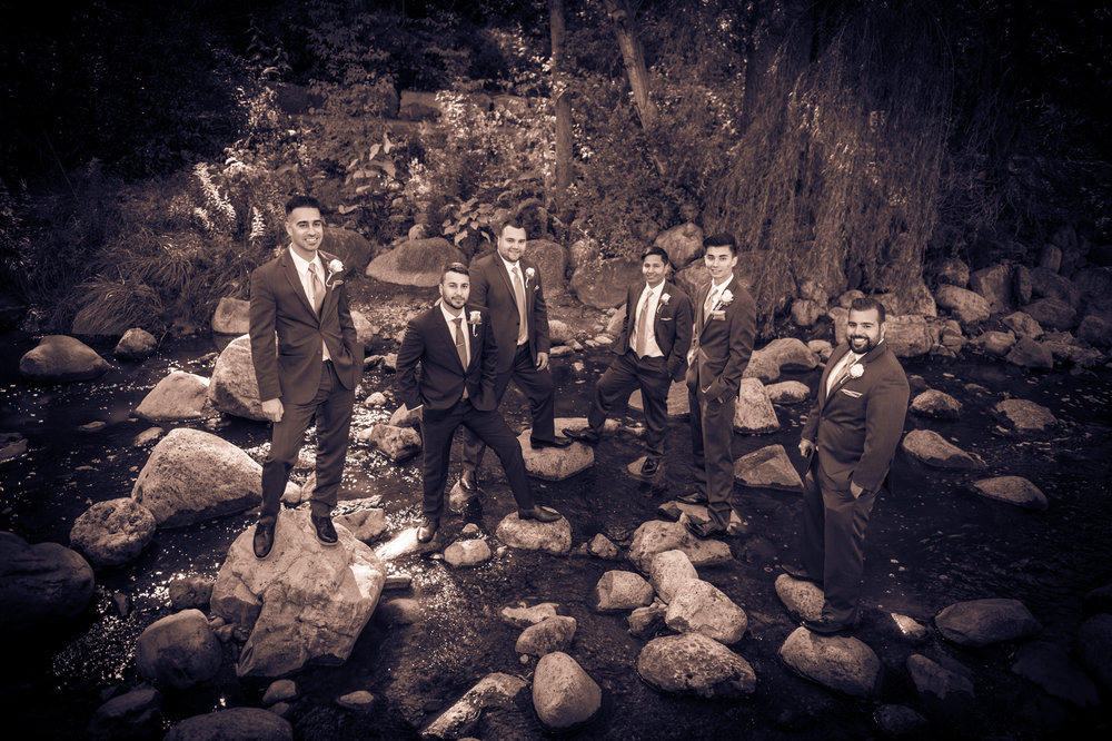 Groomsmen and Groom standing on rocks in the middle of the Don River at Edwards Gardens in Toronto