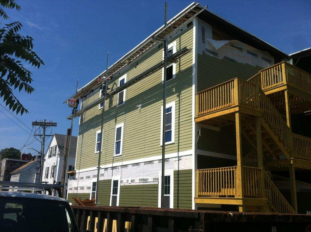 We sided the house in a two-tone green siding and added a staircase to the exterior deck so that we could remove one of the  interior staircases , creating more square footage indoors.