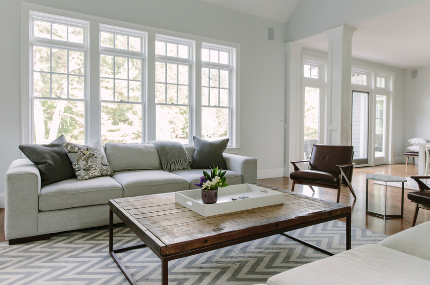 A living room designed by an interior designer with soft grays and whites as well as natural wood elements.
