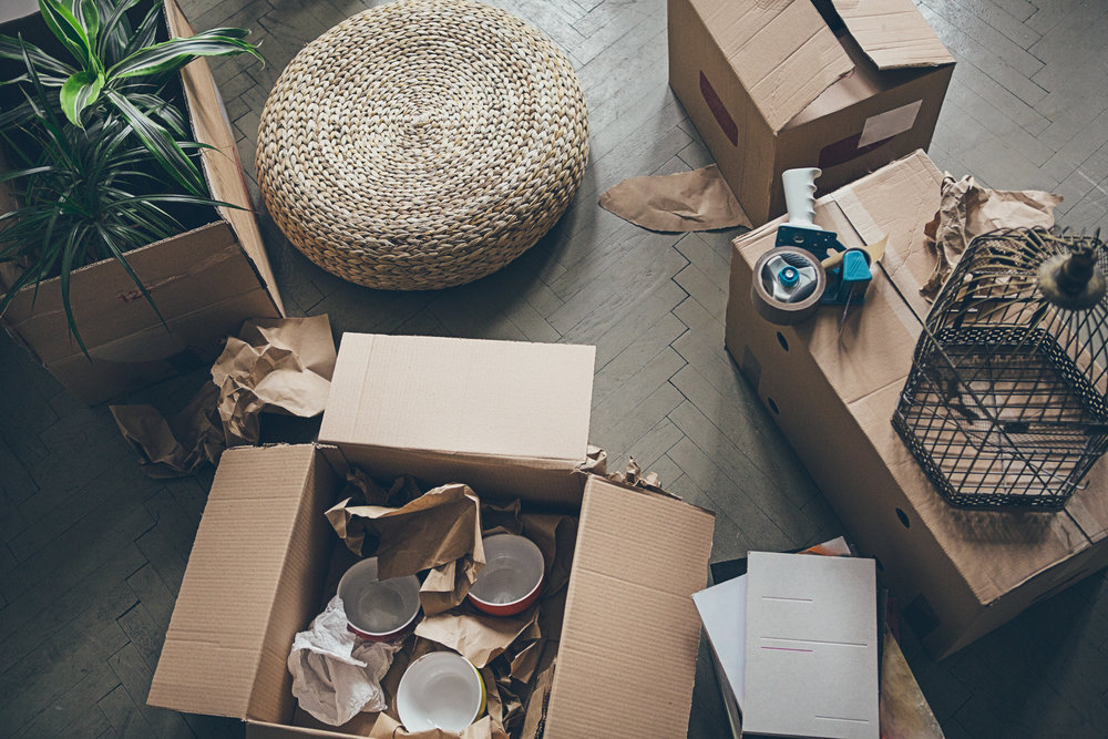 Boxes with home decorations on hardwood floors.