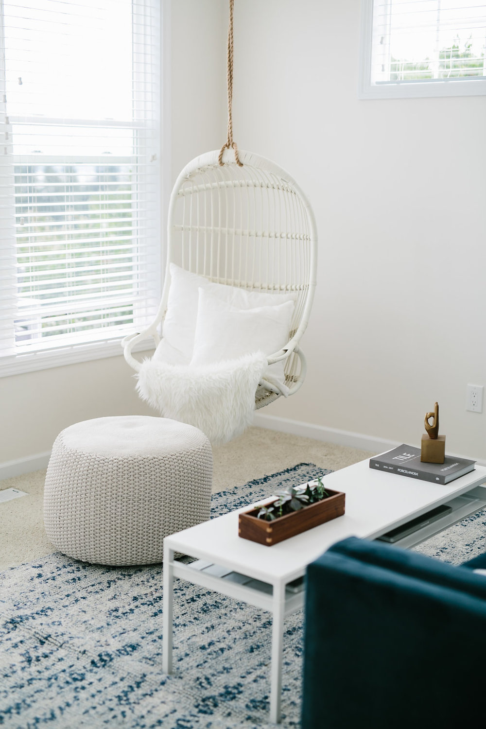 Swinging chair with a white pouf and navy blue rug.