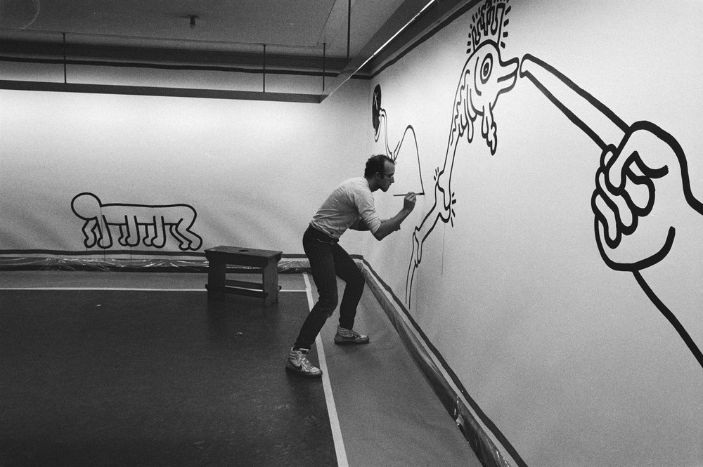 Artist Keith Harring at work on a modern line drawing in 1986 ( image source )