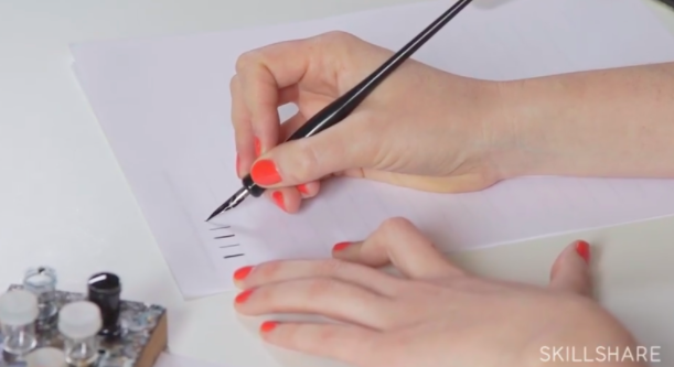 Bryn Chernoff demonstrates how to hold your nib pen at a 45-degree angle from the surface of the paper.