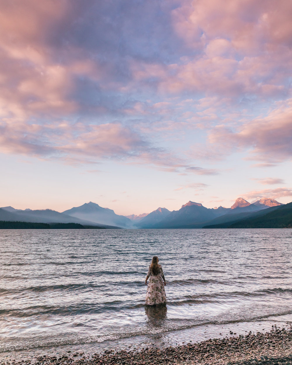 Girl in flowy dress looks at the pink sunset at Lake McDonald in Glacier National Park Montana