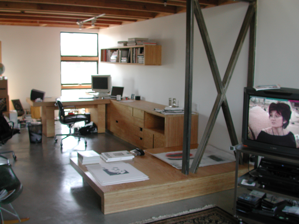 This is an-office installation designed for record executive who works primarily in the production of album art. The installation is comprised of cabinetry, a mobile desk that docks in it, a bookshelf, and a daybed that bridges the living area and the office.