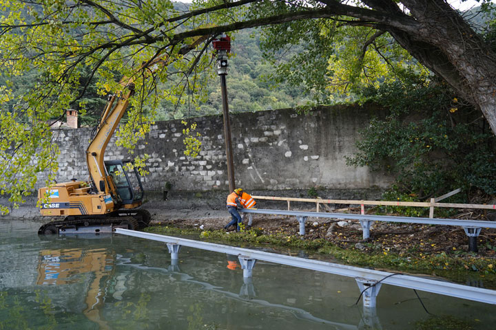 Construction workers and divers install the foundations that will support the working ramp which is used to assemble and launch the polyethylene cubes once connected