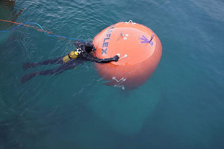 A diver positions one of the anchors before it is lowered to the ground of the lake, January 2016