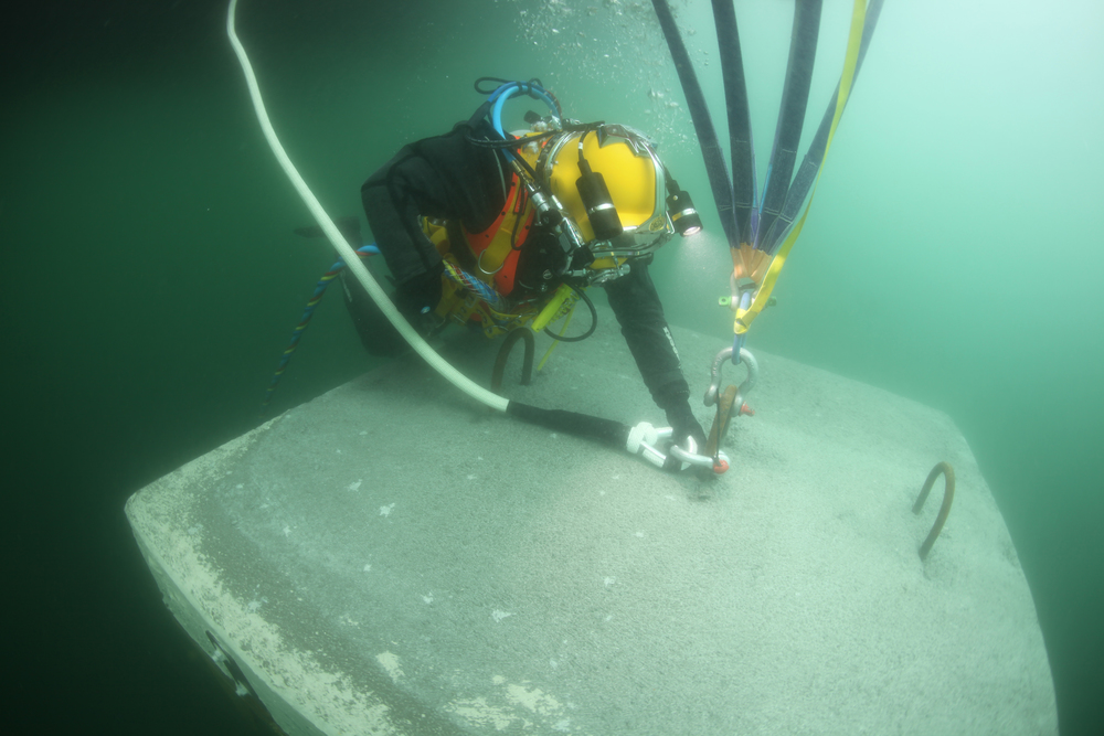 A diver connects a rope made of ultra-high-molecular-weight polyethylene, covered with a polyester protective layer with a breaking load of 20 metric tons, to keep the piers in place