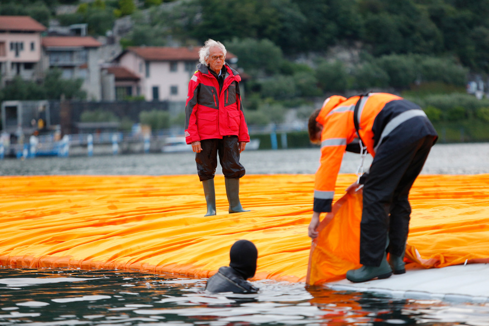 Christo is watching a diver hooking a fabric panel to the side of a floating pier, June 15, 2016