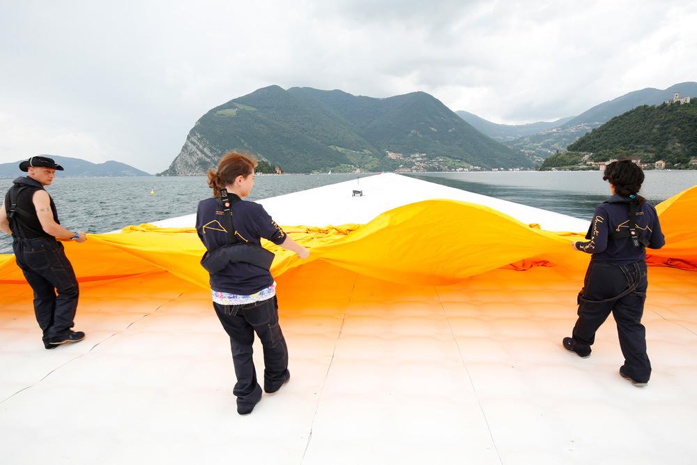 Dal 15 giugno sera fino alla sera del 17, gli addetti distendono 100.000 metri quadri di tessuto di colore giallo dalia cangiante sui pontili e sui percorsi pedonali di Sulzano e Peschiera Maraglio