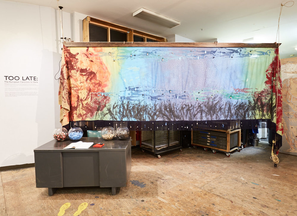 Lane Sell. Trans-Atlantic (2017). Installation of bodyprint silkscreen and sewing on hand-dyed fabric; desk, ledger, tabasco bottles, Devil's Head seeds, livestock ear tags and bells.
