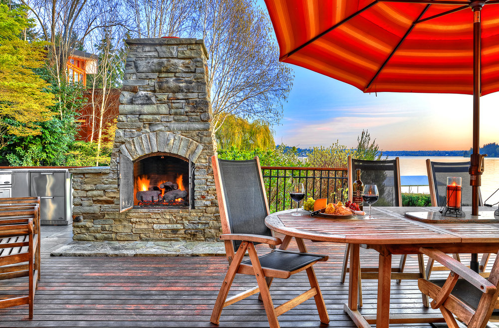 Photo of fireplace on back patio of lakefront PNW home designed by Seattle Residential Architect